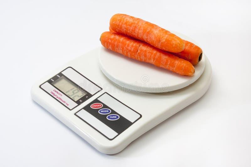 Verse wortelen op keuken digitale schaal stock afbeeldingen