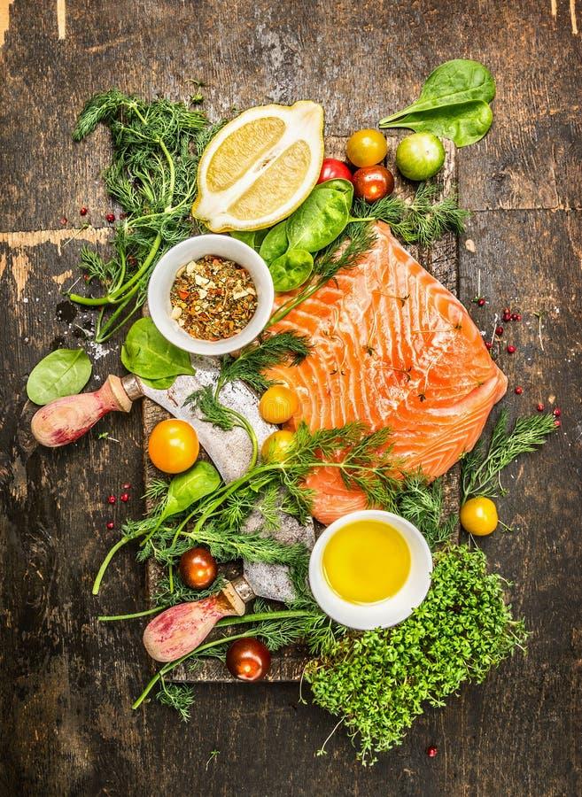 Verse zalmfilet met verse gezonde kruiden, groenten, olie en kruiden op rustieke houten achtergrond stock foto