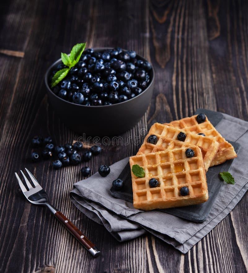 Verse zoete bosbes met aromatische Belgische waffels en honings donkere houten lijst stock afbeeldingen