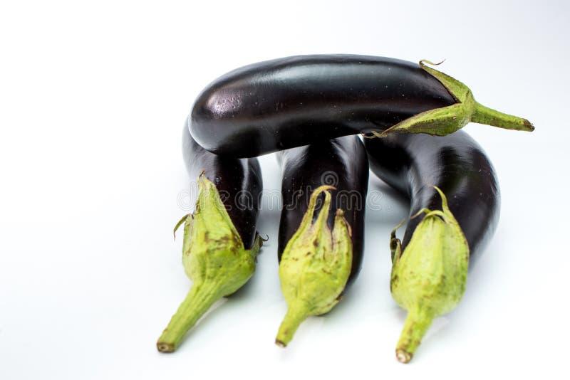 Verse zwarte die aubergine op witte achtergrond wordt ge?soleerd stock afbeeldingen