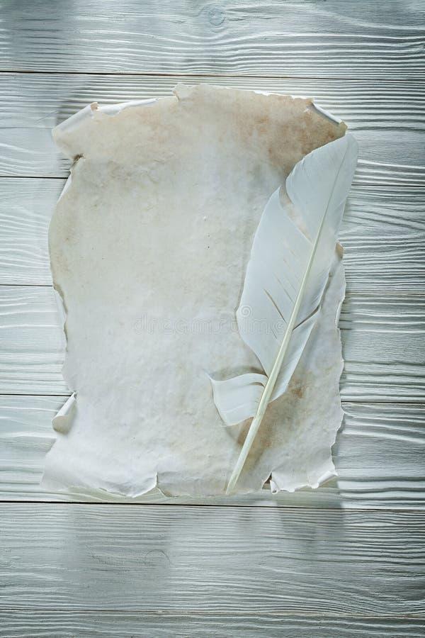 Versehen Sie Blatt des Weinleseunbeschriebenen papiers auf Vertikalenansicht des hölzernen Brettes mit Federn stockfoto