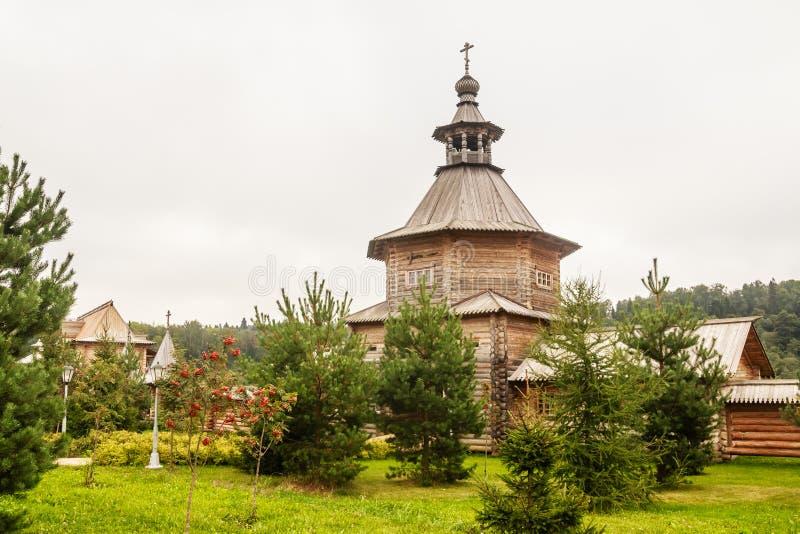 Versehen Sie hölzerne Kirche am Eingang zum heiligen Quell-Gremyachiy-Schlüssel mit einem Gatter stockfotografie
