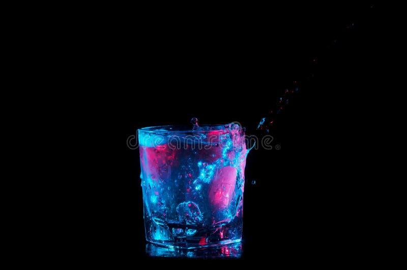 Versement du côté et éclaboussement dans des lumières de roches bleu de dessous en verre et rouge d'isolement sur un fond noir photo stock