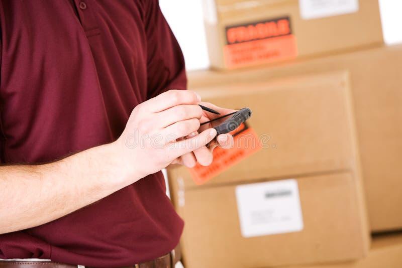 Versenden: Mann benutzt Digital-Auflage, um Pakete aufzuspüren stockbilder