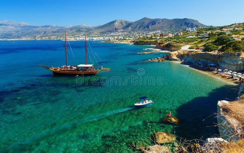Versenden Sie wie Piratenschoner mit zwei Masten für Segel nahe Felsen der Küste von Kreta stockbild