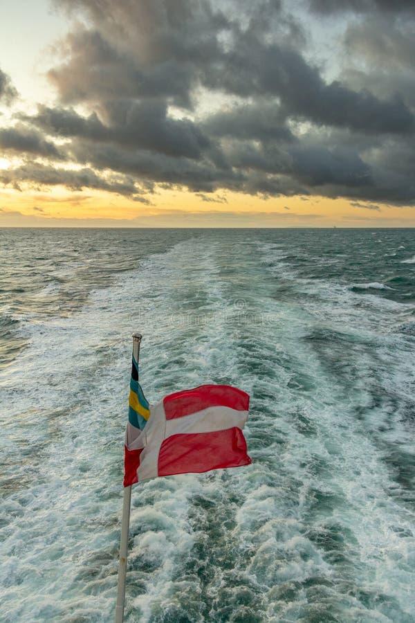 Versendet Spur und Flagge bei Sonnenuntergang stockbild