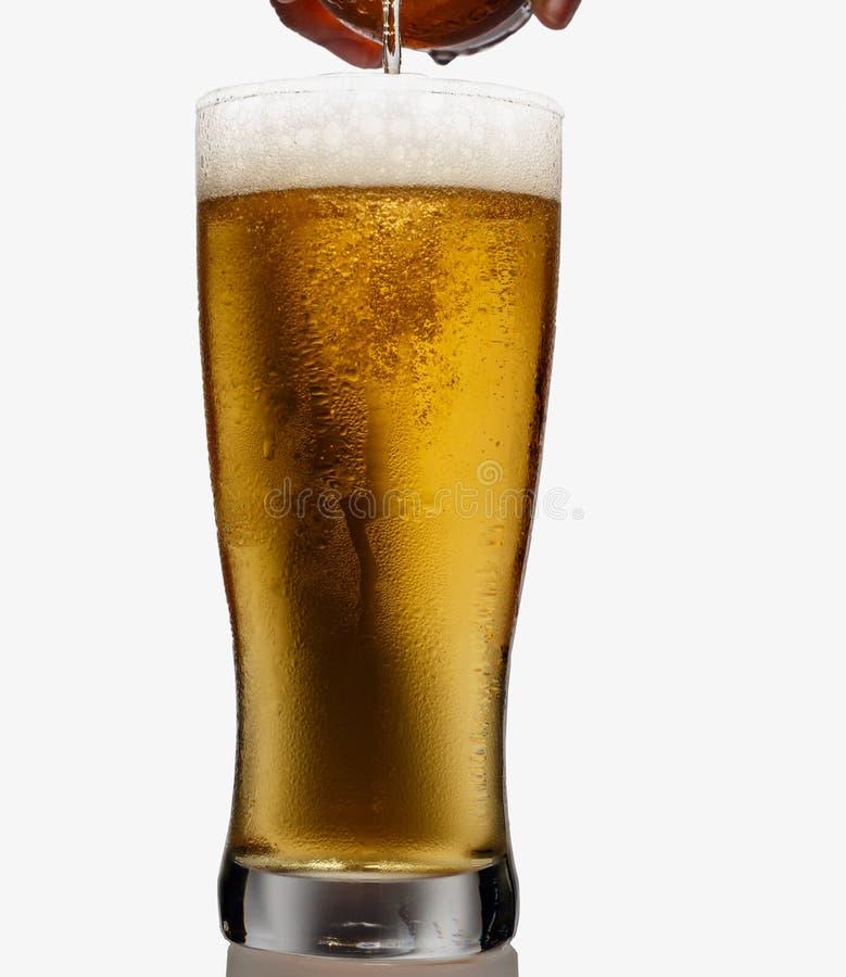Versez la bière de la bouteille dans le verre photographie stock