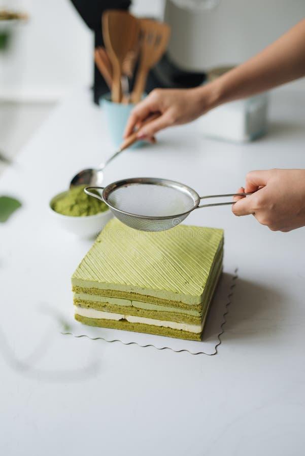 Versez la poudre de thé vert au-dessus du gâteau au fromage délicieux photos libres de droits