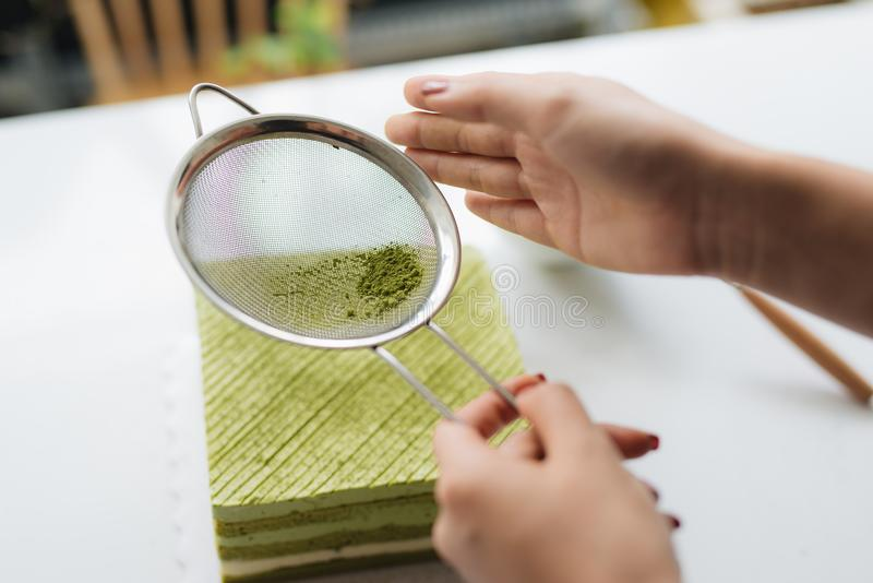 Versez la poudre de thé vert au-dessus du gâteau au fromage délicieux image libre de droits