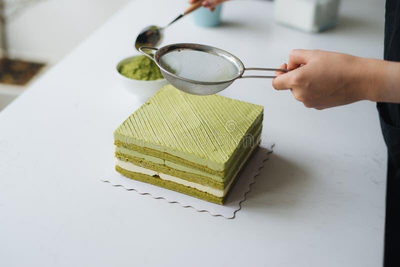 Versez la poudre de thé vert au-dessus du gâteau au fromage délicieux image stock