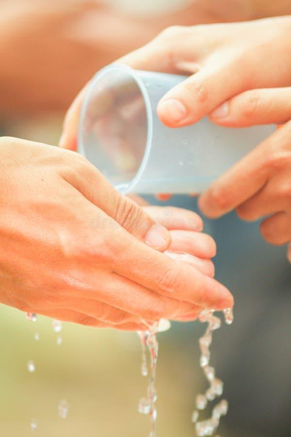 Versez une certaine eau en main photos libres de droits