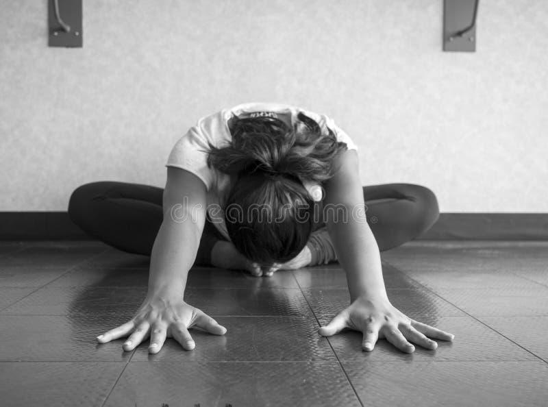 Versión blanco y negro del estiramiento de Hip del bailarín de la yoga en la posición de la mariposa que alcanza la cabeza delant imagen de archivo