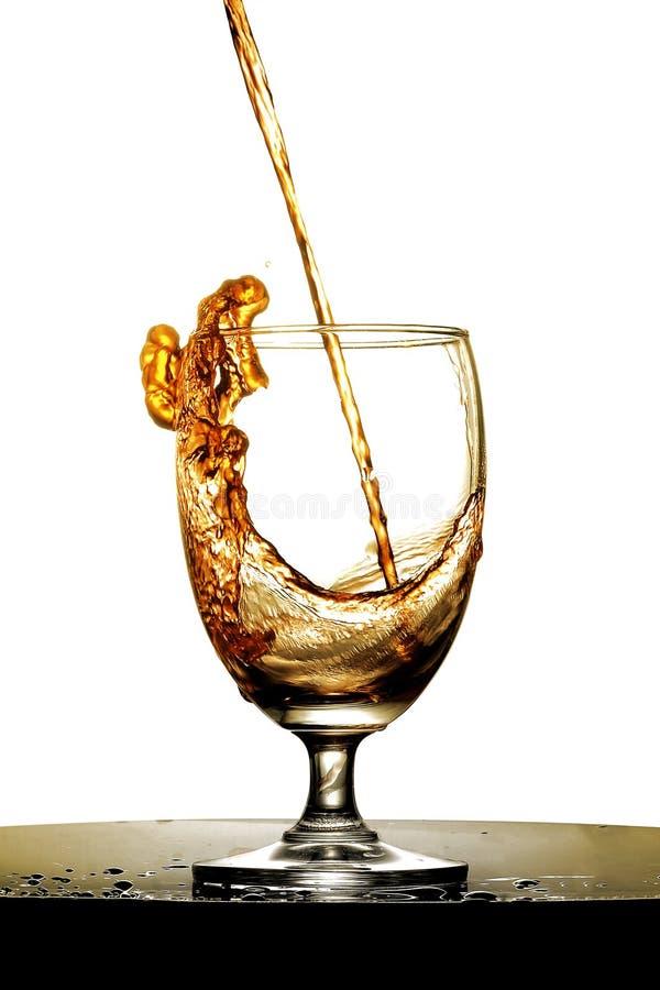 Versi il liquore ambrato in un vetro fotografia stock