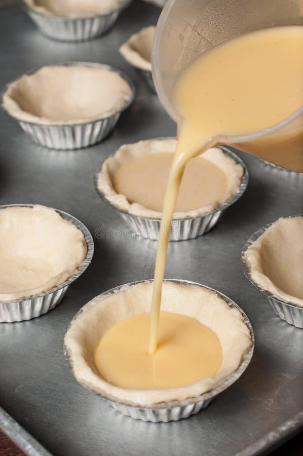 Versi la miscela della crema dell'uovo in ogni tazza acida. fotografia stock