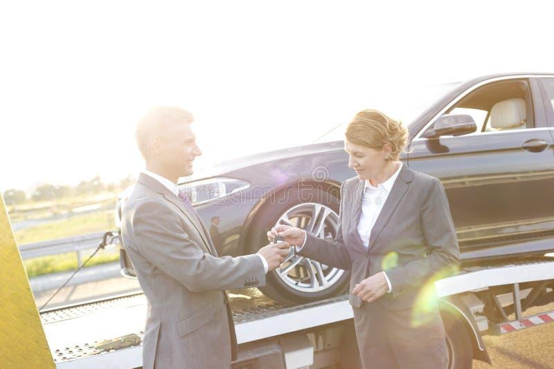 Versicherungsagent, der der Geschäftsfrau Autoschlüssel gegen Abschleppwagen gibt lizenzfreie stockbilder