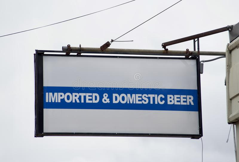 Beer Imported and Domestic. A sign outside a bar, restaurant or pub establishment advertises on a sign that it serves imported and domestic beer such as Michelob stock images