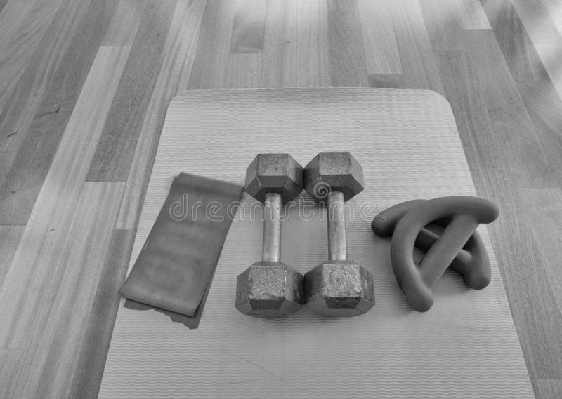 Version noire et blanche de vue aérienne d'une paire des haltères, des bandes d'exercice de theraband, et d'un tapis de yoga sur  photographie stock