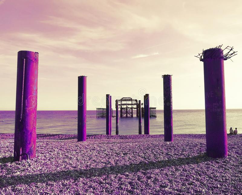 Version pourpre artistique de Brighton West Pier et des piliers photos stock