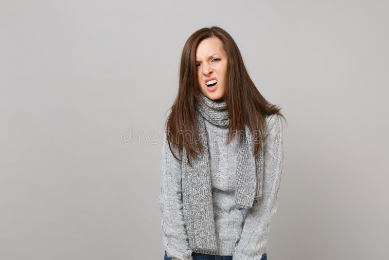 Verslagen uitgeputte geïrriteerde jonge vrouw in grijze sweater, sjaal op grijs achtergrondstudioportret Gezond stock fotografie