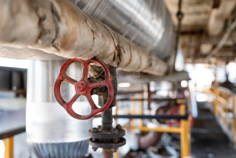 Versleten staalvangst in de workshop van een raffinaderij met een rode klep royalty-vrije stock foto
