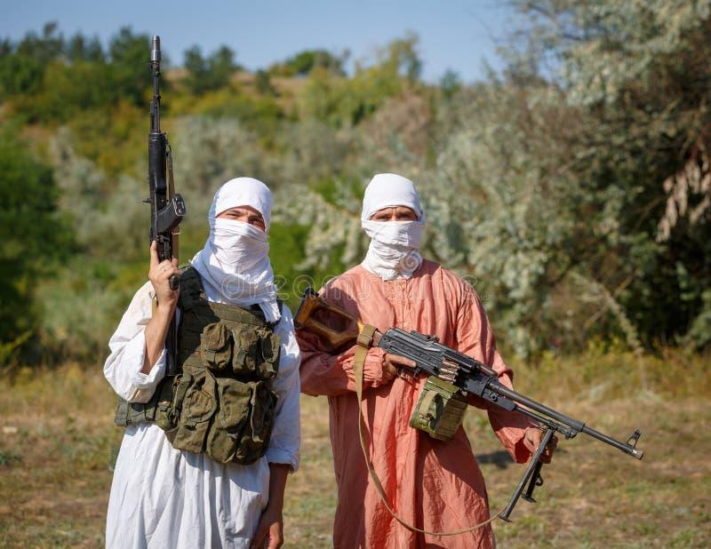 Versluierde militairen in traditionele moslimkleren met kanonnen in hun handen stock afbeelding