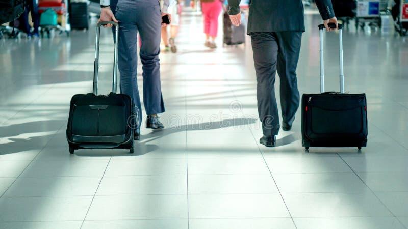 Verso borrado do homem de negócio 2 que anda no terminal de aeroporto com espaço do efeito e da cópia da luz do alargamento imagens de stock