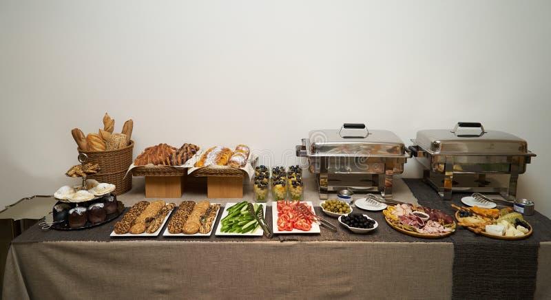 Versorgende Hochzeitsbuffet-Nahrungsmitteltabelle auf grauem Wandhintergrund lizenzfreie stockbilder