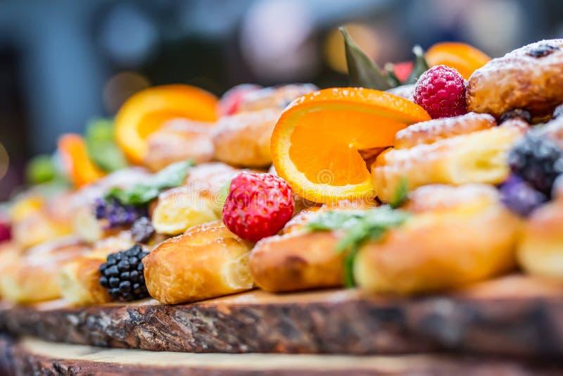 Versorgendes Buffetlebensmittel im Freien Beerenorangentrauben der frischen Früchte der Kuchen bunte und Krautdekorationen lizenzfreies stockbild