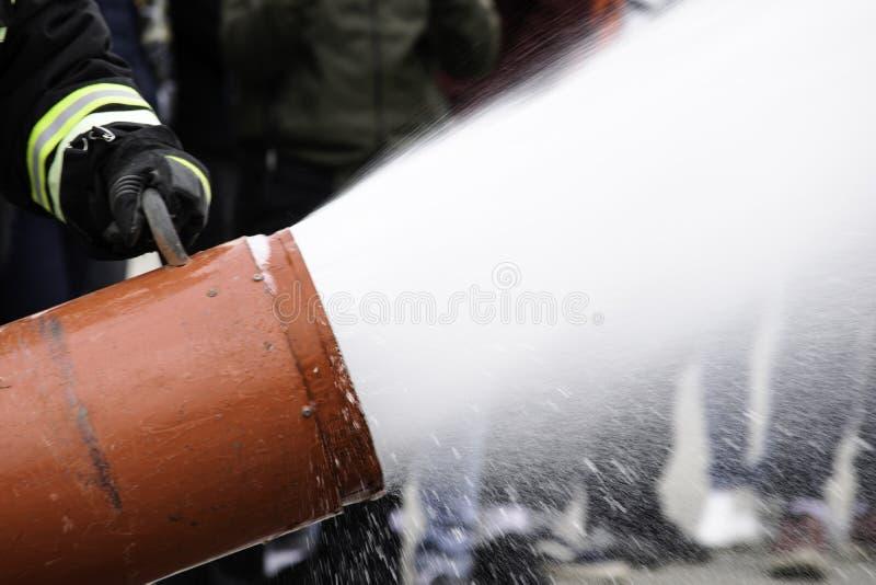 Versorgung Schaum von einem Schaumgenerator, Feuerlöschschaum fliegt vom Schaumgenerator, der den Feuerwehrmann im Kampf hält lizenzfreies stockfoto