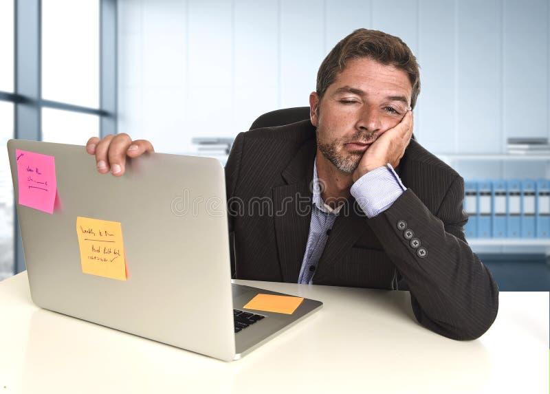Verspilde zakenman die in spanning bij bureaulaptop computer werken die uitgeput kijken stock afbeeldingen