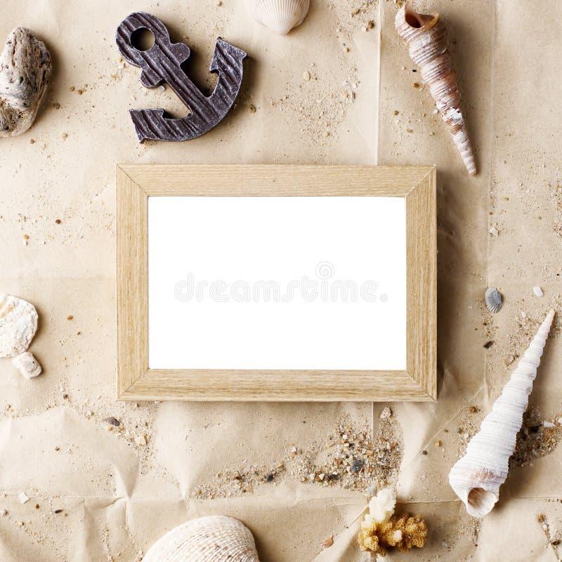 Verspotten hölzerner Fotorahmen der Weinlese auf Kraftpapier mit Sand- und Seeoberteilen oben lizenzfreies stockfoto