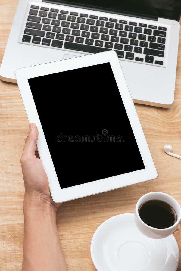 Verspotten Sie herauf Bild einer Hand, die schwarzen Tabletten-PC mit weißem leerem Bildschirm und Kaffeetasse auf Holztischhinte stockbilder