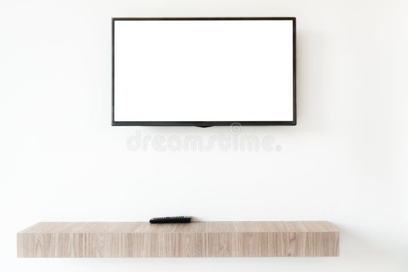 Verspotten Sie herauf flachen Fernsehschirm mit Fernplatte wwden an Regal im livin stockfotos