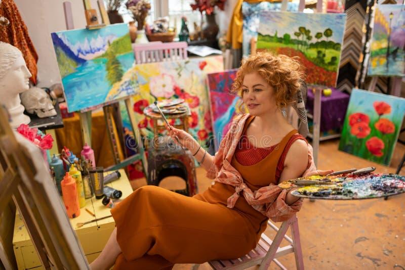 Versprechender Künstler, der ihr Bild sitzt und betrachtet stockbild