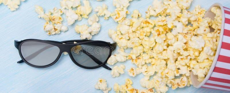 Verspreid op een lichtgrijze achtergrond, popcorn in een emmer en 3 glazen van D stock fotografie