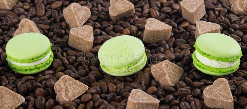 Verspreide koffiebonen, met drie munt macaron koekjes, suikerhart, achtergronddag van alle minnaars royalty-vrije stock afbeelding