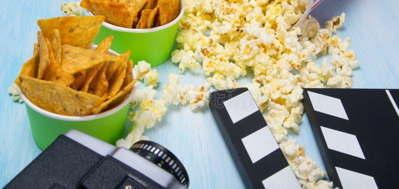 Verspreide popcorn, op een blauwe achtergrond, naast een oude videocamera, een dubbel voor opnameinformatie en een emmer van heer royalty-vrije stock fotografie