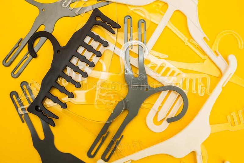Verspreide witte en grijze hangers op gele achtergrond stock foto