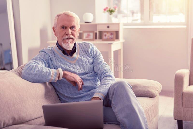 Verständnisvoller älterer Mann, der blaue einfache Strickjacke trägt lizenzfreies stockbild