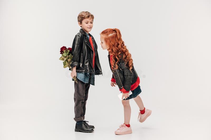 versteckende Rosen des Jungen für seine kleine Rückseite der Freundin hinten lizenzfreie stockfotos
