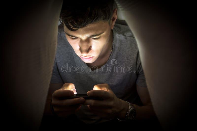 Versteckender Teenager bei der Anwendung eines Handys lizenzfreie stockbilder