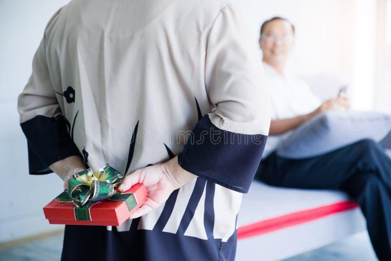 Versteckendes Geschenk der älteren Frau für ihren Ehemann hinter Rückseite auf valentineday Älteres Paarasien-Feiern anniversaryd lizenzfreies stockbild