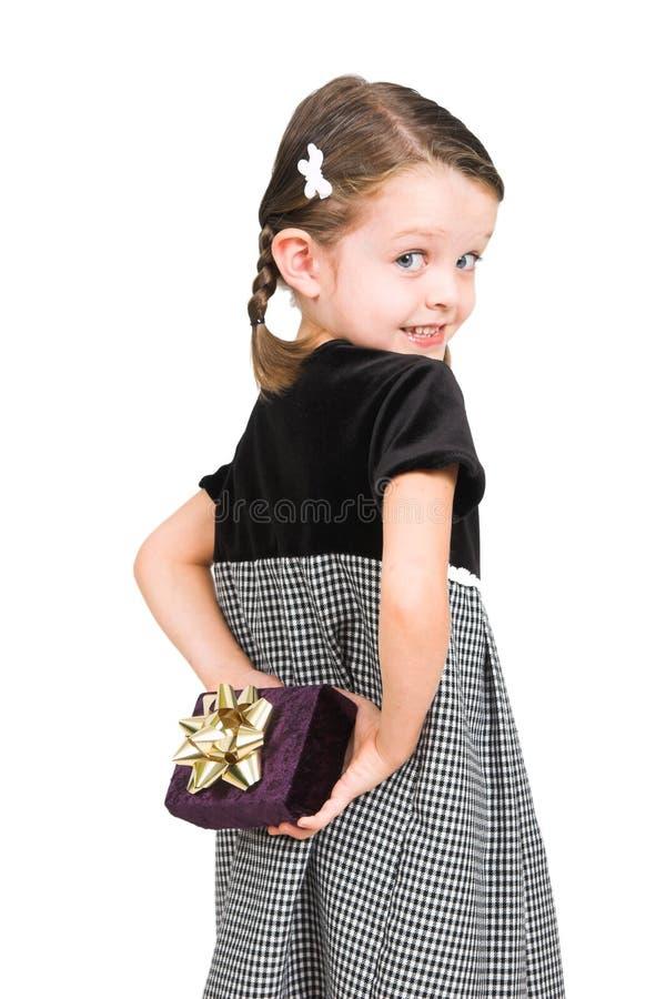 Versteckendes Geschenk des kleinen Mädchens lizenzfreie stockfotos