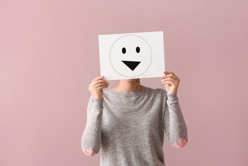 Versteckendes Gesicht der jungen Frau hinter Blatt Papier mit gezogenem Emoticon auf Farbhintergrund lizenzfreie stockfotografie