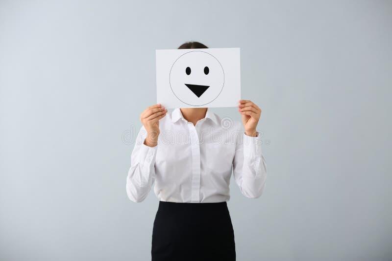 Versteckendes Gesicht der jungen Frau hinter Blatt Papier mit gezogenem Emoticon auf hellem Hintergrund stockfotos