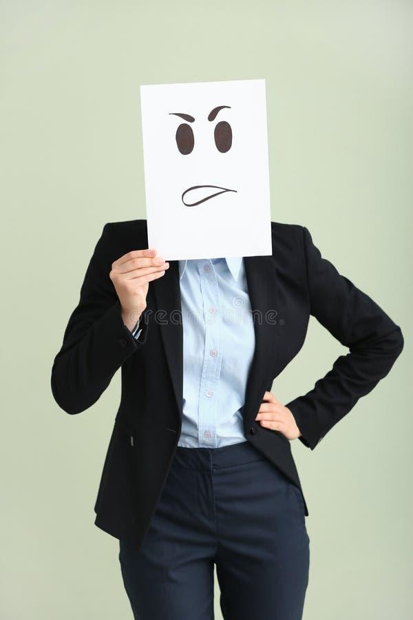 Versteckendes Gesicht der jungen Frau hinter Blatt Papier mit gezogenem Emoticon auf hellem Hintergrund lizenzfreie stockfotos