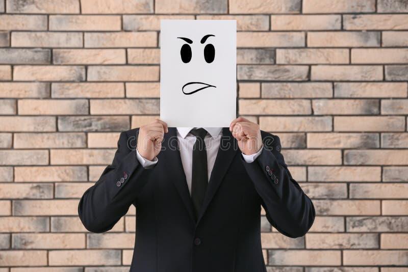 Versteckendes Gesicht des Geschäftsmannes hinter Blatt Papier mit gezogenem Emoticon gegen Backsteinmauer lizenzfreies stockbild