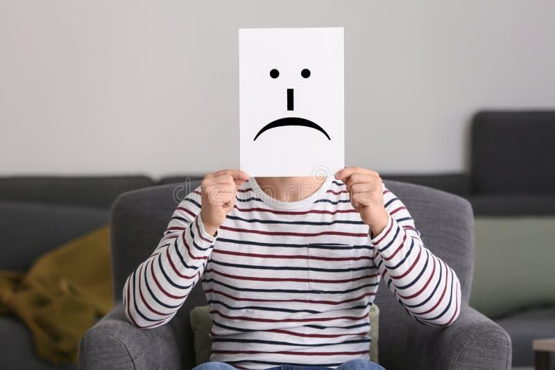 Versteckendes Gesicht des jungen Mannes hinter Blatt Papier mit gezogenem Emoticon beim im Lehnsessel zu Hause sitzen stockfotografie