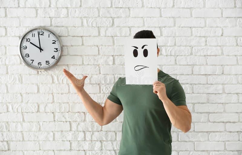 Versteckendes Gesicht des jungen Mannes hinter Blatt Papier mit gezogenem Emoticon gegen weiße Backsteinmauer mit Uhr lizenzfreie stockbilder