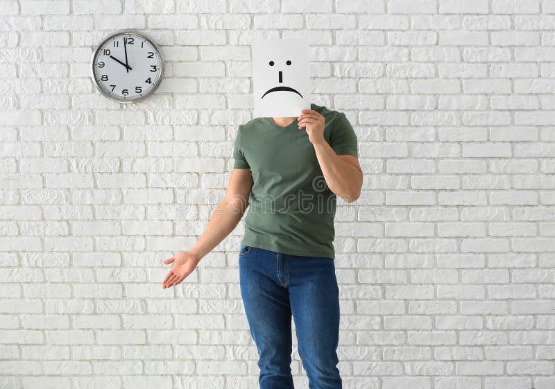 Versteckendes Gesicht des jungen Mannes hinter Blatt Papier mit gezogenem Emoticon gegen weiße Backsteinmauer mit Uhr stockfotos